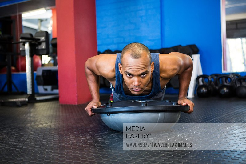 Portrait of stern male athlete with BOSU ball while exercising in gym