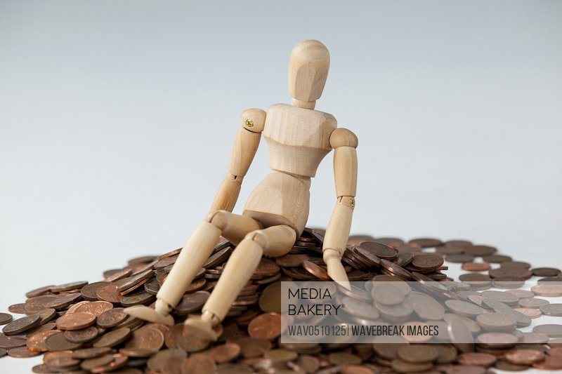 Wooden figurine sitting on heap of coins against white background