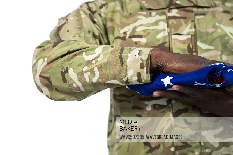 Mid section of soldier holding an american flag against white background