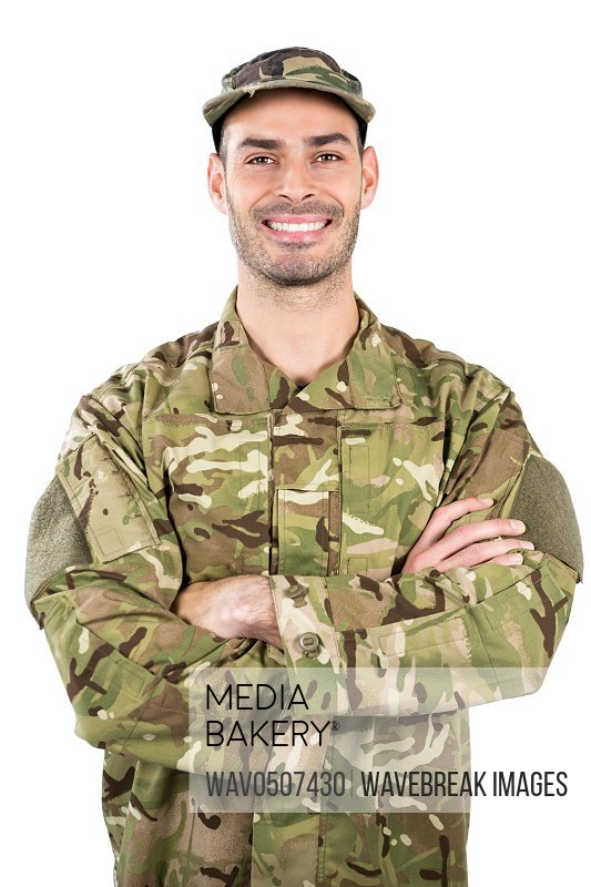Portrait of smiling soldier standing with arms crossed against white background