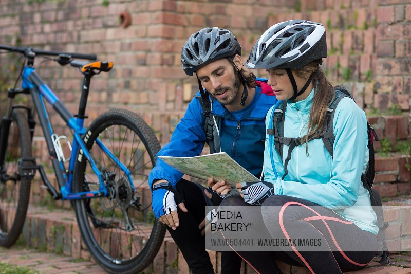 Biker couple looking at a map in countryside