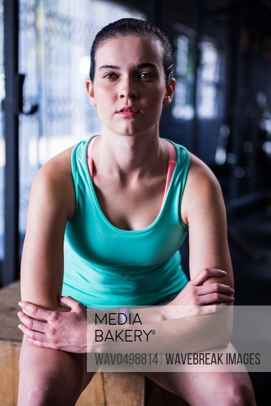 Portrait of confident young athlete sitting in gym