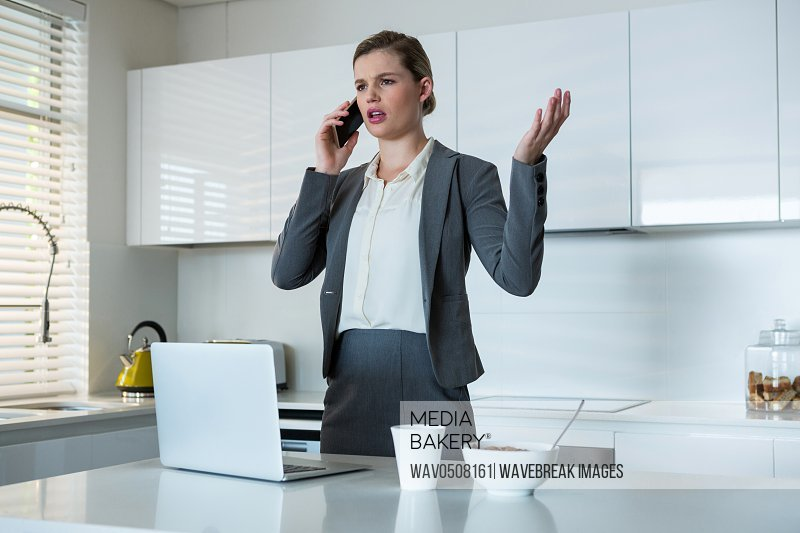 Woman talking on mobile phone in kitchen at home