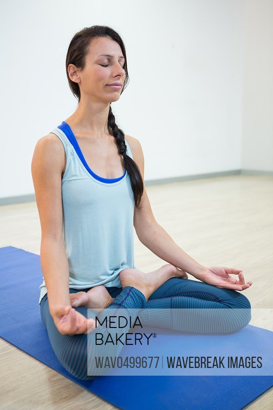 Woman practicing yoga in lotus position in fitness studio