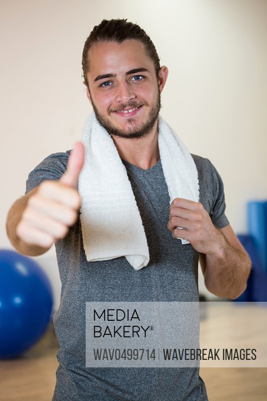 Portrait of smiling man showing thumbs up in fitness studio