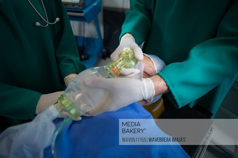 Surgeons placing oxygen mask on patient mouth in operation theater