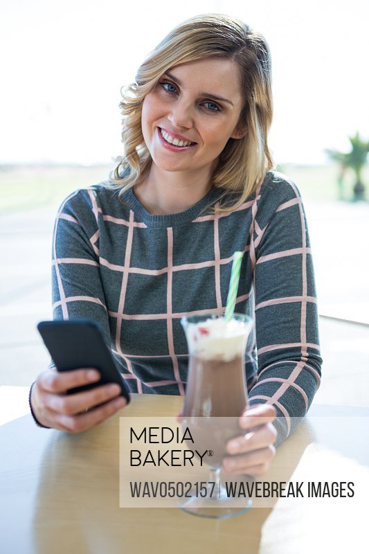 Portrait of smiling woman using mobile phone while having milkshake in cafeteria