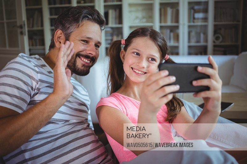Smiling father and daughter looking at mobile phone in living room at home