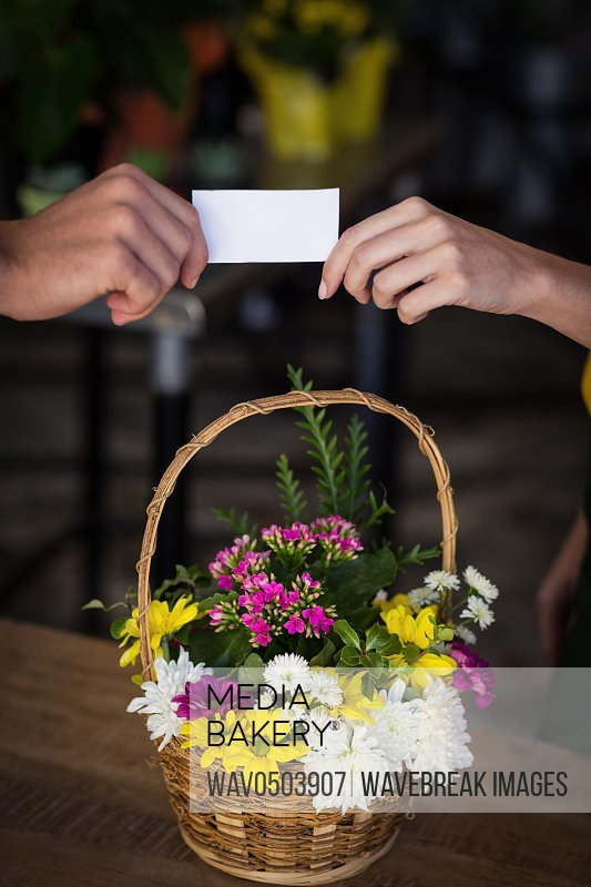 Female florist giving visiting card to customer in the flower shop