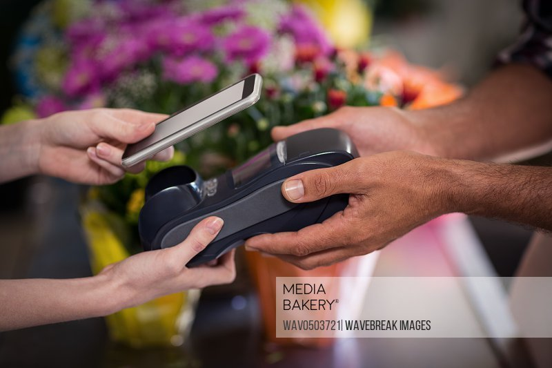 Hand of customer making payment through smartphone in the flower shop