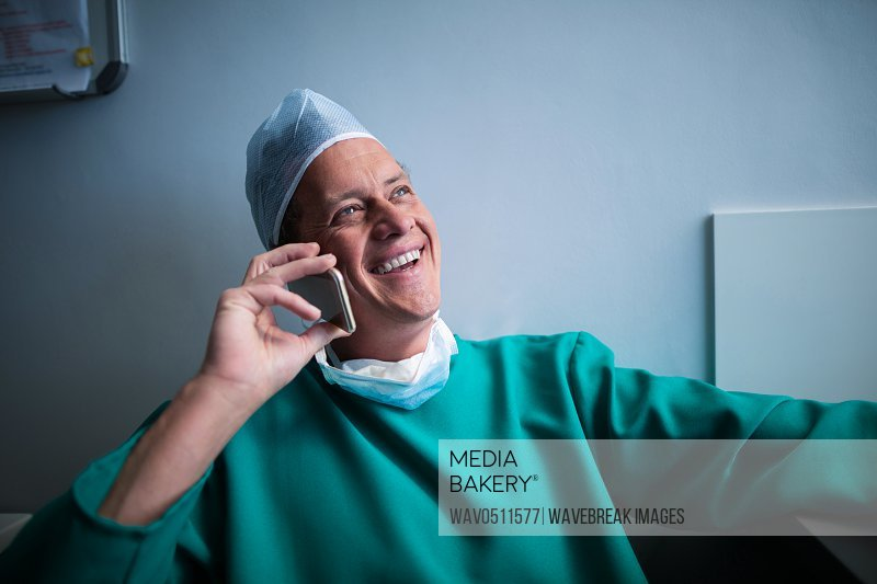 Smiling surgeon talking on mobile phone in hospital