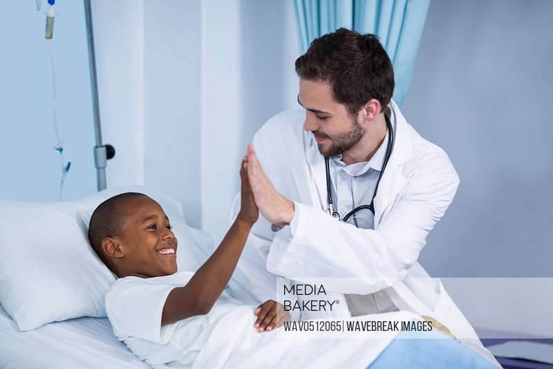 Doctor and patient giving high five in hospital