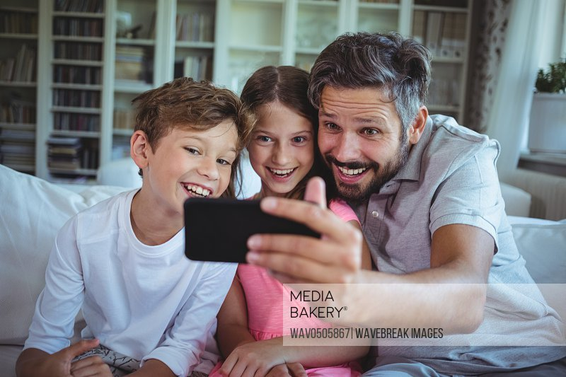 Father sitting on sofa with his children and clicking a selfie in living room at home
