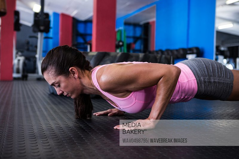 Side view of athlete woman doing push-ups in gym