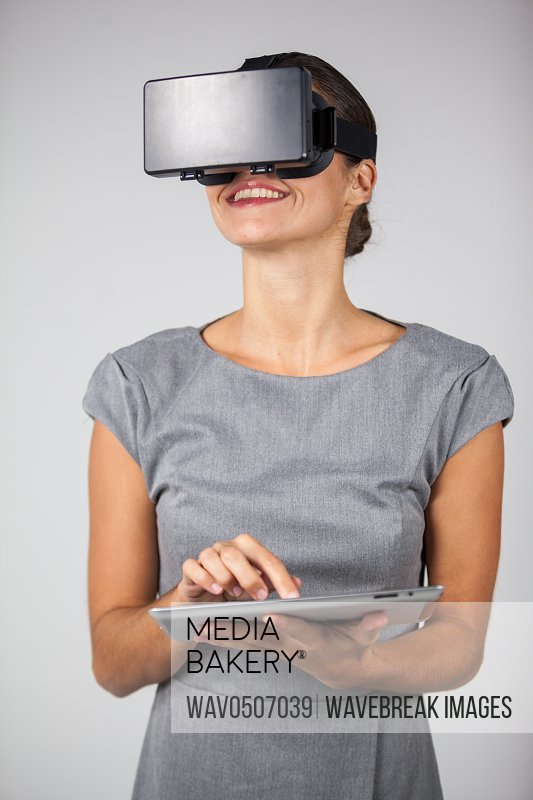 Woman holding digital tablet and using virtual reality headset against white background
