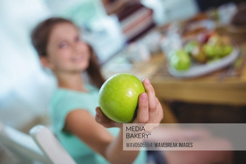 Smiling girl showing a green apple at home