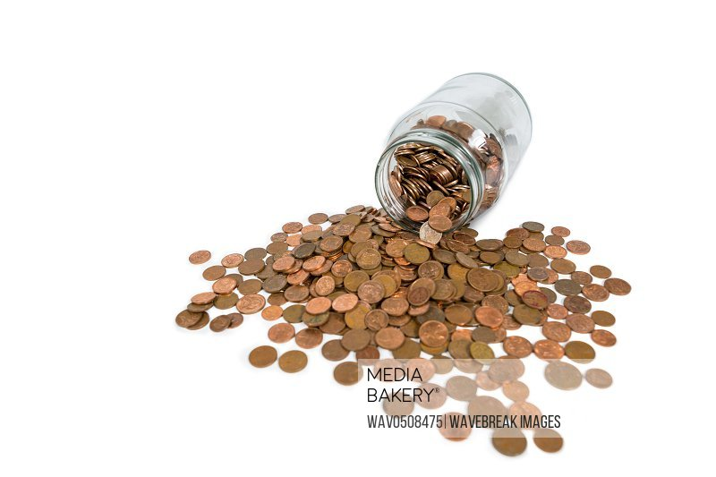Coins spilling out of glass jar on white background