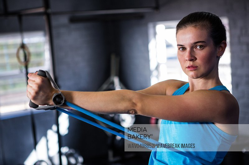 Portrait of female athlete stretching resistance band while standing in gym