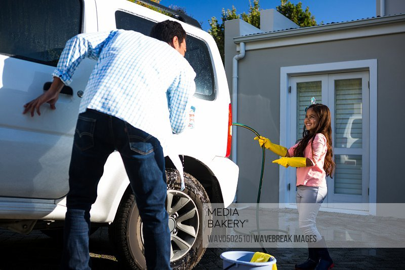 Father and daughter washing car together outside house
