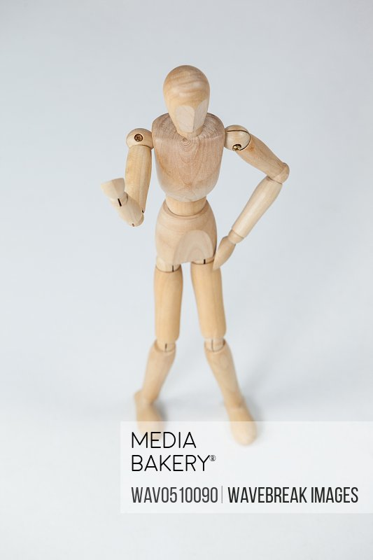 Wooden figurine standing and showing his fist against white background