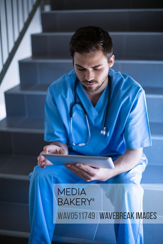 Male nurse sitting on staircase and using digital tablet of hospital