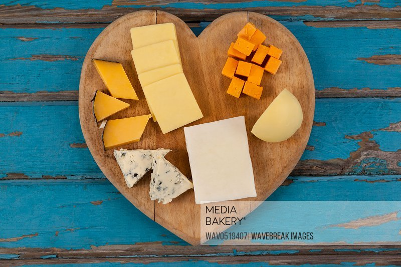 Variety of cheese on heart shaped chopping board