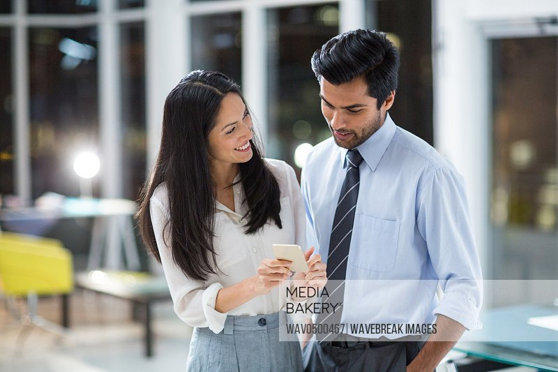 Businesswoman showing mobile phone to colleague in the office