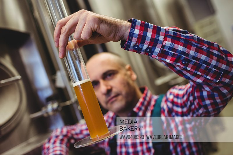 Owner examining beer in glass tube at brewery
