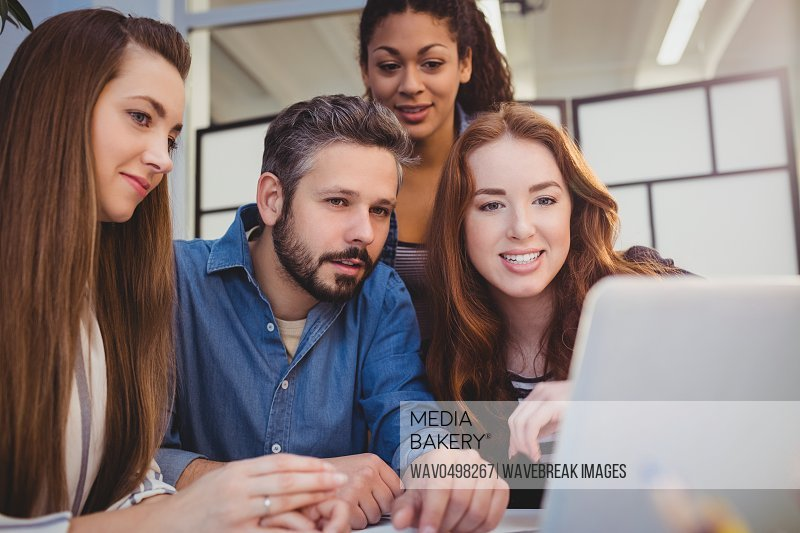 Smiling creative business people using laptop at desk in office