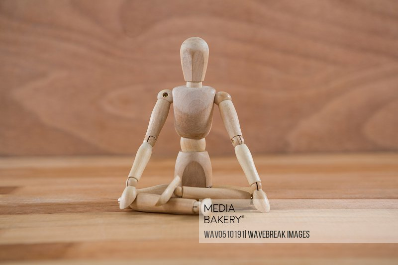 Wooden figurine sitting in a lotus position on wooden floor