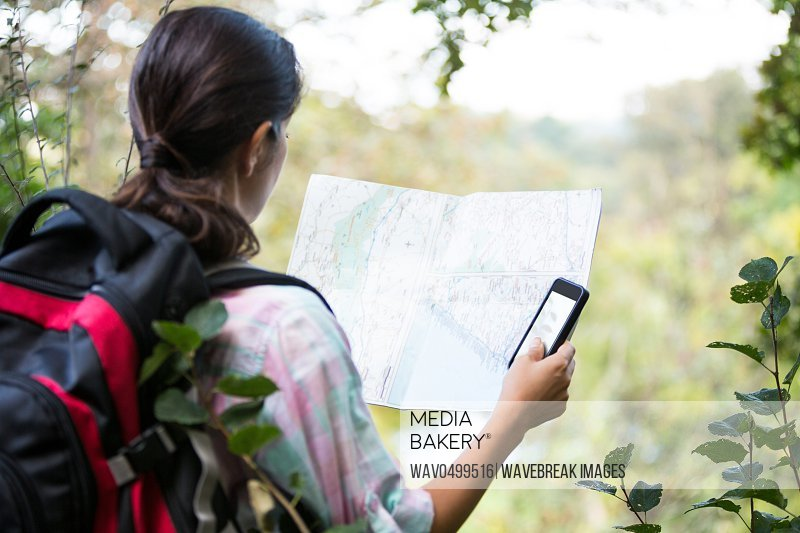 Female hiker looking at map in forest