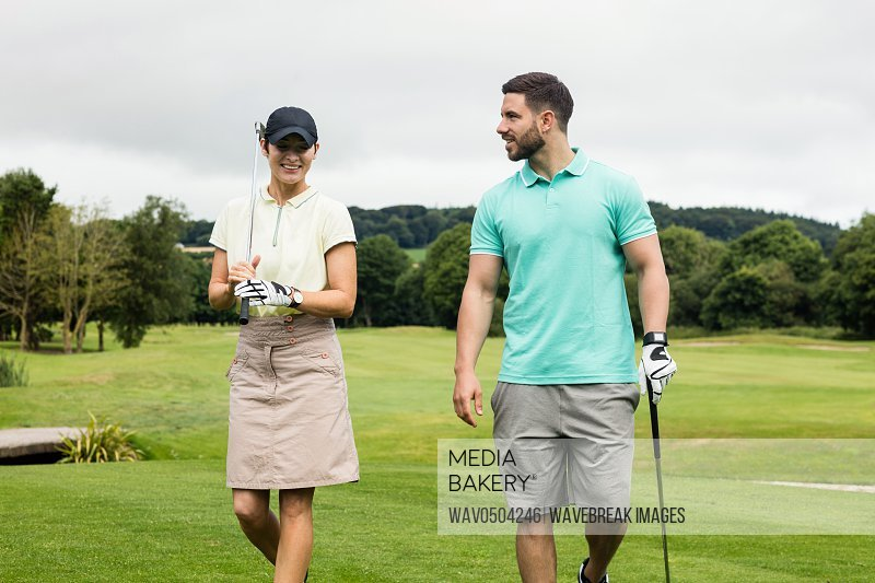 Couple interacting with each other while walking in golf course