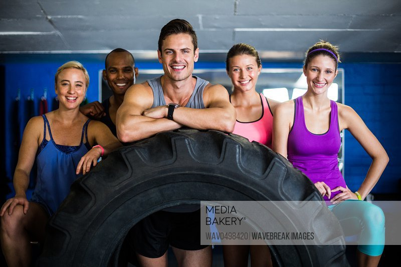 Portrait of smiling friends with tire while standing in gym