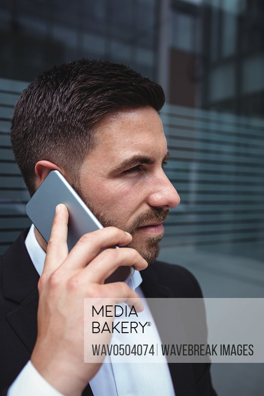 Businessman talking on mobile phone in the office building