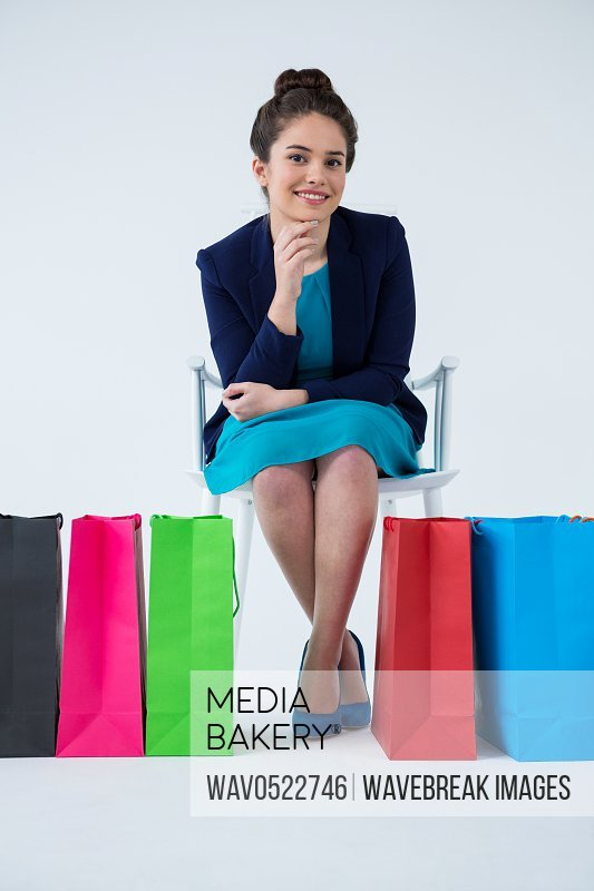 Woman sitting with colorful shopping bags