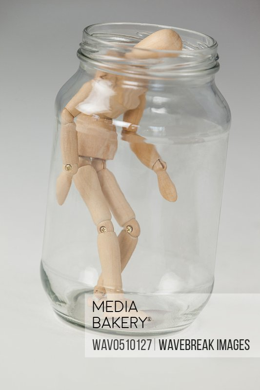 Wooden figurine standing inside a glass jar against white background