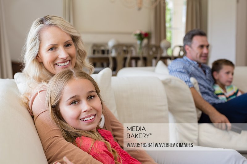 Smiling mother and daughter sitting together in living room