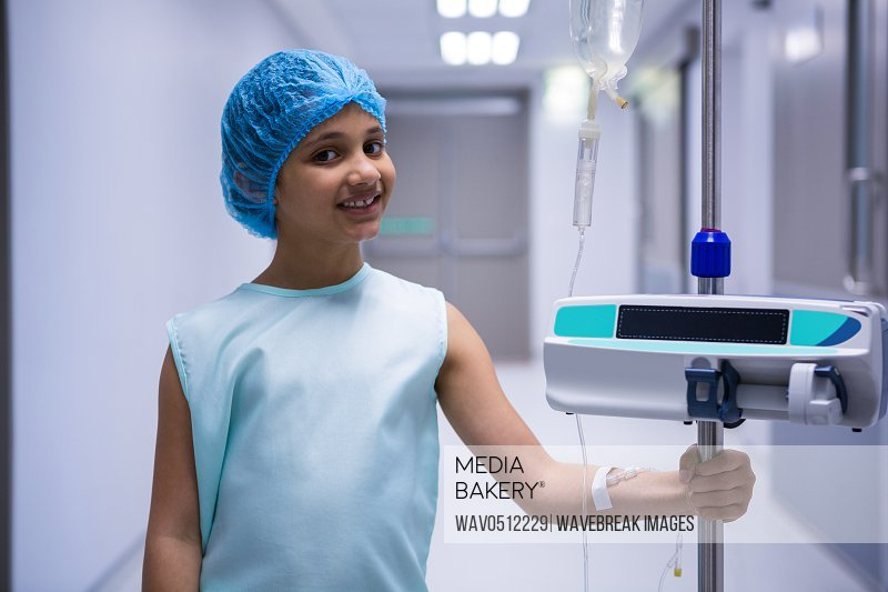 Portrait of smiling girl with iv drip standing in corridor at hospital