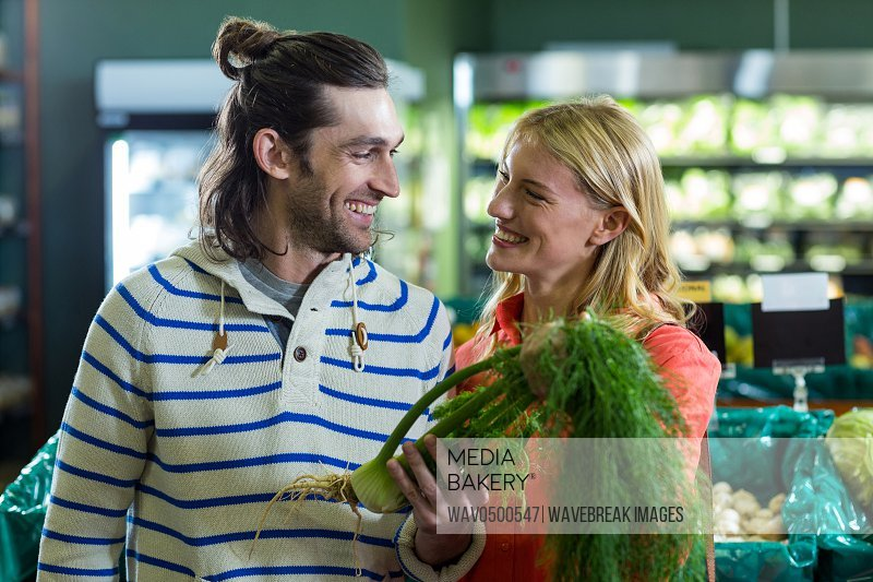 Happy couple holding fennel in organic section of supermarket