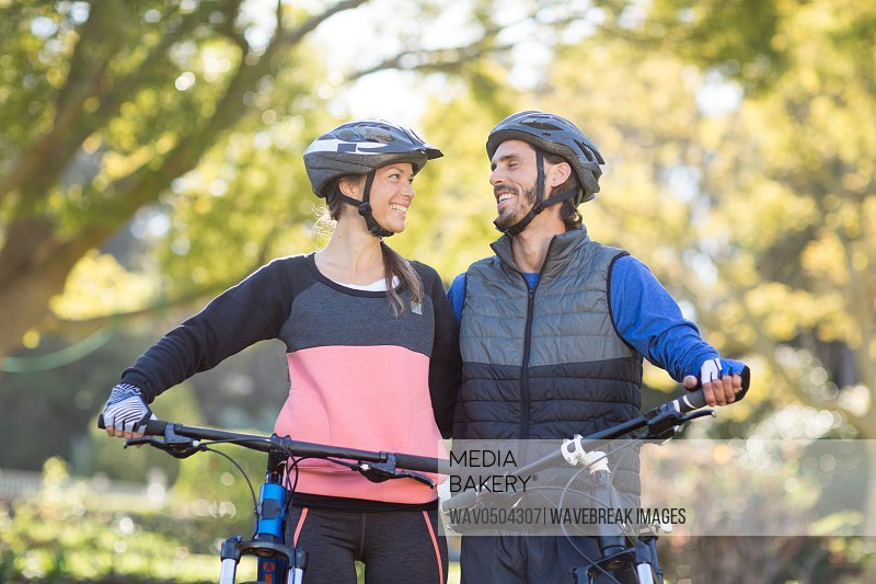 Biker couple standing with mountain bike in countryside