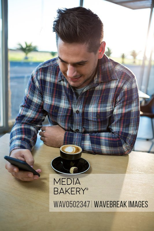 Man with coffee on the table using his mobile phone in the coffee shop