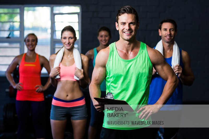 Portrait of smiling fitness instructor holding clipboard while people standing in background