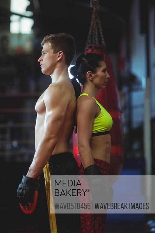 Female and male boxer standing back to back in fitness studio