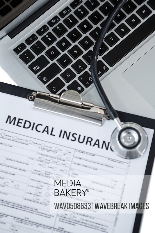 Clipboard with medical insurance paper stethoscope and laptop