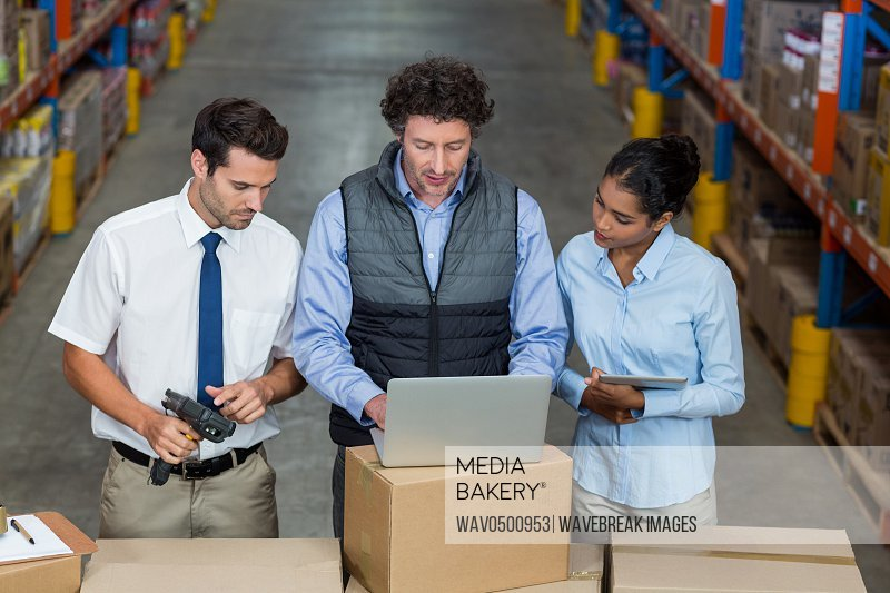 Warehouse workers and manager discussing with laptop in the warehouse