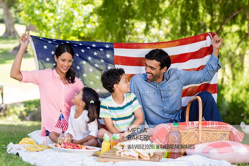 Happy family holding a american flag in park