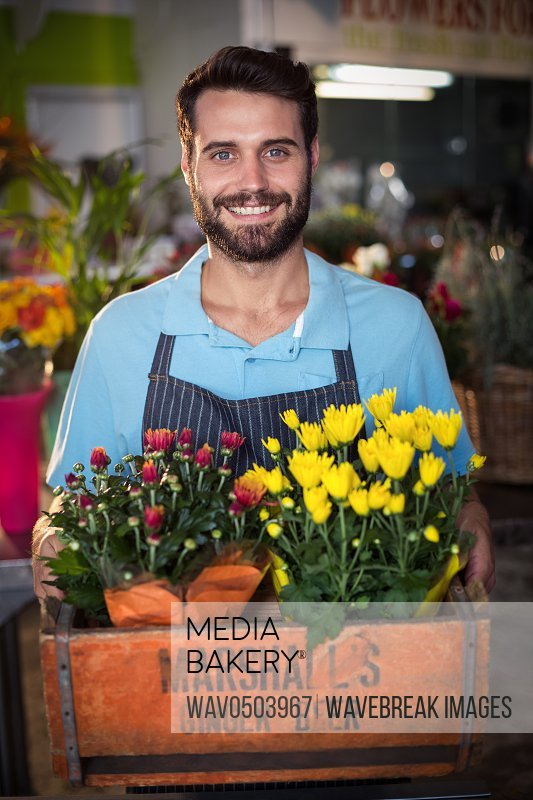 Male florist holding crate of flower bouquet in the flower shop