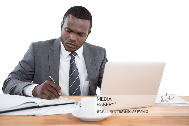 Concentrated businessman working at office desk against white background