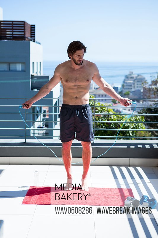 Man exercising with skipping ropes in balcony at home
