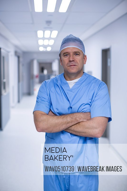 Portrait of male surgeon standing with arms crossed at the hospital